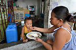 "In the capital of the Philippines, a mother feeds her child in the doorway of a mausoleum that doubles as their home in the Manila North Cemetery. Hundreds of poor families live here, dwelling in and between the tombs and mausoleums of the city's wealthy. They are often discriminated against, and many of their children don't go to school because they're too hungry to study and they're often called ""vampires"" by their classmates. With support from United Methodist Women, KKFI provides classroom education and meals to kids from the cemetery at a nearby United Methodist Church."