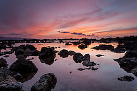 A colorful sunset reflects off calm water among rocks at Shark's Cove on the North Shore of O'ahu