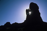 Silhouette of rock formation with sunburst through crack-Arches National Park, Utah