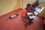 While a younger sibling sleeps on the floor behind them, students study in a classroom in the Loreto Primary School in Rumbek, South Sudan. While the school, run by the Institute for the Blessed Virgin Mary--the Loreto Sisters--of Ireland, focuses on educating girls from throughout the war-torn country, it also educates children from nearby communities.