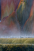 Fine art nature abstract of Fly Geyser, a/k/a Fly Ranch Geyser, near Gerlach in Washoe County, Nevada, showing 2 layers of base rings of travertine mound on which geyser sits and continues to grow, with layers being pummeled by showers of water spray and water drops coming from top of geyser not shown in image, with brilliant reds, oranges, yellows and greens caused by thermophilic algae flourishing under varying temperatures of hot, geothermal water; access to ranch was by permission.