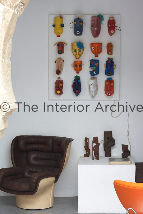 A retro brown leather chair stands next to a wooden block displaying ethnic inspired figurines in the open living area