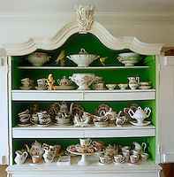In the living room of this 18th century house in Holland a collection of Staffordshire porcelain is displayed in an antique cupboard painted in vivid green and white