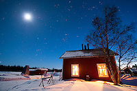 "Solberget, Jokkmokk, Swedish Lapland, Sweden, March 2013. Spectacular Northern Lights, also known as Aurora Borealis, over Solberget. Dirk and Silke Hagenbusch live their lives in a wilderness retreat  called 'Solberget'. It is situated directly on the Arctic Circle, near the nature reserves ""Granlandet"", ""Päivavuoma"" and ""Pellokiellas"", and close to the ""Muddus"" National Park. Here, nature can be experienced in its purest form – far away from civilisation. As an authentic wilderness farm, Solberget is neither connected to public electricity nor to the mains water supply. Water comes from a spring in the woods and is delicious! Oil lamps and the natural warmth of wood burning stoves provides a soft and cosy atmosphere, even with biting frost outside. Photo by Frits Meyst/Adventure4ever.com"
