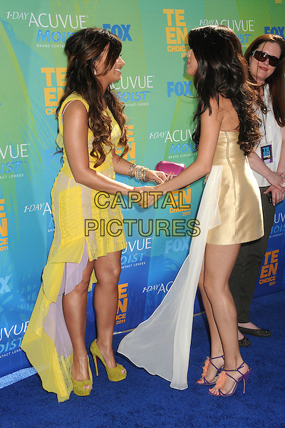 Demi Lovato & Selena Gomez.2011 Teen Choice Awards - Arrivals held at Gibson Amphitheatre, , Universal City, California, USA..August 7th, 2011.full length dress yellow lace train gold white strapless smiling laughing side profile pink clutch bag.CAP/ADM/BP.©Byron Purvis/AdMedia/Capital Pictures.