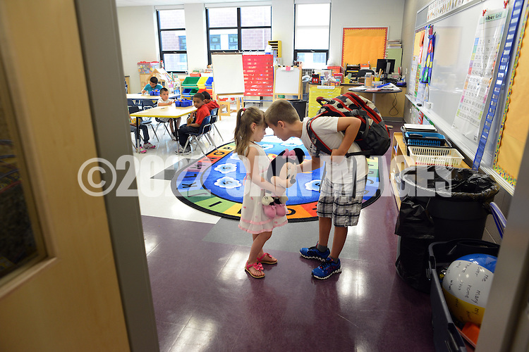 WARMINSTER, PA - SEPTEMBER 3: Bogdan Zadorozhnyy (right), 10, consoles his younger sister Julia Zadorozhna, 5, after they arrived for the first day of school September 3, 2013 at the new McDonald Elementary School in Warminster, Pennsylvania. (Photo by William Thomas Cain/Freelance)
