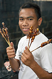 INDONESIA, Flores, portrait of Tarsi holding chicken skewers in the kitchen at Lucas restaurant in Bajawa