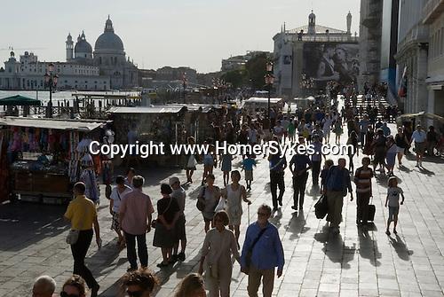Venice Italy 2009. Tourists walk  along the Pizzetta at Saint Marks Square, Piazza San Marco. The church of Santa Maria della Salute.