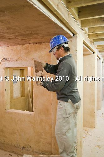 Plastering student applies plaster overhead, Able Skills, Dartford, Kent.