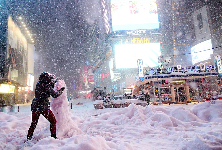 NEW YORK - JANUARY 23: A woman helps decorate a snowman built in Times Square on January 23, 2016 in New York, after a huge snow storm slammed into the Mid-Atlantic States.  (Photo by Yana Paskova)