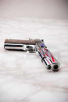Handgun laying on marble surface with American flag reflected in barrel