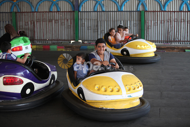 """Palestinians play at an amusement park during the fourth day of Eid al-Adha or """"Feast of the sacrifice"""" in Gaza City on September 27, 2015. Muslims across the world are celebrating the annual festival of Eid al-Adha which marks the end of the Hajj pilgrimage to Mecca and is held in commemoration of Prophet Abraham's readiness to sacrifice his son to show obedience to God. Photo by Ashraf Amra"""