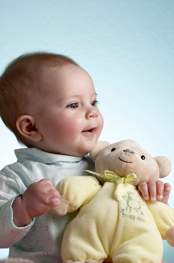 Portrait of 6 month old baby girl sitting with teddy bear