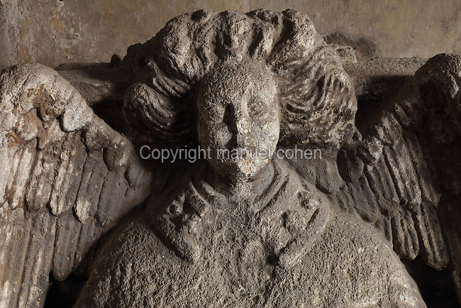 Sculpted angel on a tombstone of a canon in the vaulted chapterhouse off the cloister, in the Cathedrale Notre-Dame du Puy, or Le Puy Cathedral, Le Puy-en-Velay, Haute-Loire, Rhone-Alpes-Auvergne, France. The cathedral was built 11th - 13th century in Romanesque style, with a striking striped 3-layered facade and large cloister. It is a national monument and UNESCO World Heritage Site as part of the Santiago de Compostela pilgrimage route. Picture by Manuel Cohen