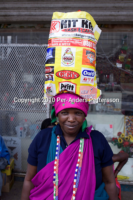 SOWETO, SOUTH AFRICA - JANUARY 14: An unidentified woman carries a bag on her head at an informal market on January 14, 2010, in the Kliptown section of Soweto, South Africa. Soweto is the largest township in South Africa, located about 10 kilometers southwest of downtown Johannesburg. The population is estimated to be around 2-3 million. A growing black middle class can be seen in the township and many shopping malls and has been built the last few years. (Photo by Per-Anders Pettersson/Getty Images)