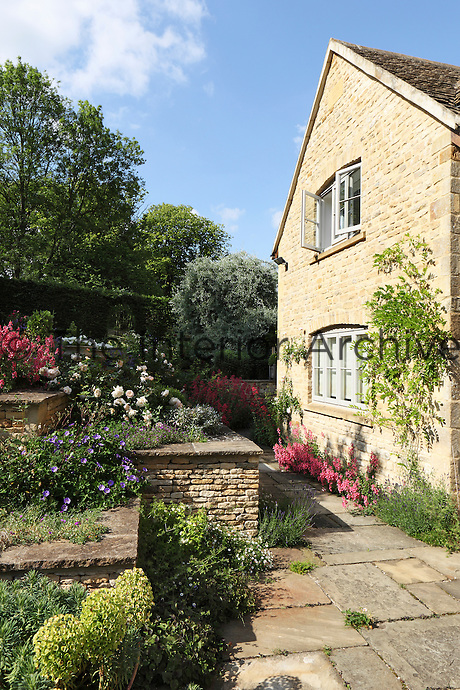 Tiers of raised flowerbeds abundant with colourful plants step up from the patio area near the house