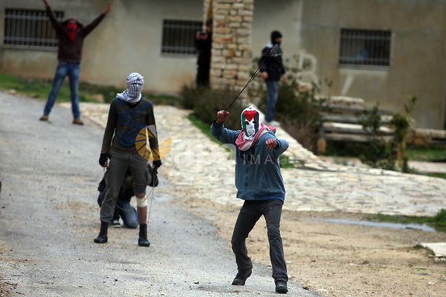 A Palestinian protester hurls stone at Israeli troops during a demonstration against the expansion of the nearby Jewish settlement of Halamish in the West Bank village of Nabi Saleh near Ramallah, Friday, Feb. 10, 2012. Photo by Issam Rimawi
