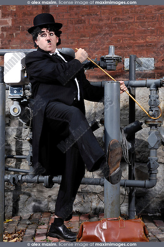 Charlie Chaplin mime damaging a gas pipe with his cane. Artistic humorous concept. Performing artist Peter Jarvis. Toronto Canada.