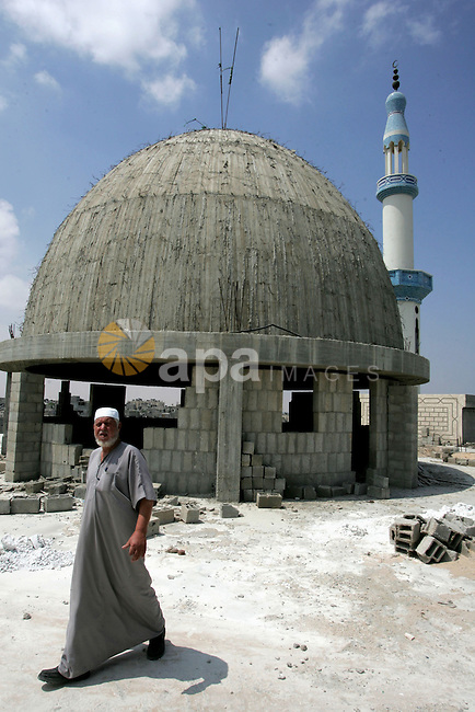 A Palestinian man walks in the construction area at Al-Abrar mosque on the fourth day of the holy month of Ramadan in the southern Gaza Strip town of Rafah on August 14,2010. Al-Abrar Mosque was destroyed by Israeli airstrike during the Israeli offensive on Gaza Strip. Photo by Khaled Khaled