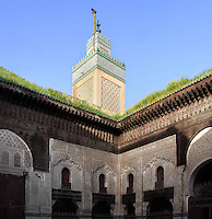 Low angle view of minaret above corner of courtyard, Bou Inania Madrasa, Fez, Morocco, pictured on February 25, 2009 in the morning. The Bou Inania Madrasa was founded as a boarding school and mosque in AD 1351-56 by Abu Inan Faris, also the founder of the Bou Inania Madrasa in Meknes, and holds the status of Grand Mosque. A fine example of Marenid architecture with its intricate plasterwork, carved cedar and decorated tiles or zellij it is the only mosque in Fez open to non-Muslim visitors. It was renovated in the 18th and 20th centuries. Fez, Morocco's second largest city, and one of the four imperial cities, was founded in 789 by Idris I on the banks of the River Fez. The oldest university in the world is here and the city is still the Moroccan cultural and spiritual centre. Fez has three sectors: the oldest part, the walled city of Fes-el-Bali, houses Morocco's largest medina and is a UNESCO World Heritage Site;  Fes-el-Jedid was founded in 1244 as a new capital by the Merenid dynasty, and contains the Mellah, or Jewish quarter; Ville Nouvelle was built by the French who took over most of Morocco in 1912 and transferred the capital to Rabat. Picture by Manuel Cohen.