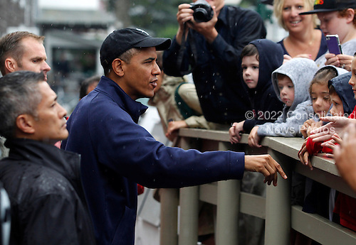 United States President Barack Obama, chats with onlookers in front of Nancy's Restaurant before placing a take-out order in Oak Bluffs, Massachusetts on the island of Martha's Vineyard on August 13, 2013.  President Obama and his family are spending the week on the island for their summer vacation.  <br /> Credit: Matthew Healey / Pool via CNP