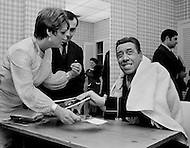 Manhattan, New York City, USA. February 15th, 1968. French comedian Fernandel signing photographs backstage at New York City's Carnegie Hall.