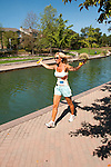 USA, Indiana, Indianapolis, jogger exercising along tree-lined canal in downtown area with architectural features and housing..