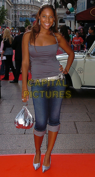 "SU-ELISE NASH.""Herbie: Fully Loaded"" UK Premiere, Vue West End, WC2..July 28th, 2005.full length jeans denim rolled up cropped three quarter length silver metallic bag purse belt hand on hip grey gray singlet.www.capitalpictures.com.sales@capitalpictures.com.©Capital Pictures"