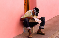 Abstract of old man reading newspaper with pink walls in Havana Cuba Habana