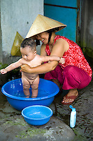 A Vietnamese mother giving her baby a sponge bath along the banks of the Mekong River.  Never mind the onlookers and photo happy tourists - this is just natural everyday life in Vietnam.