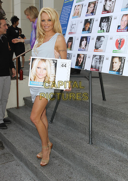 Pamela Anderson.PETA Goes Postal: Bob Barker and Pamela Anderson unveil vegetarian icons postage sheets, Hollywood Post Office, Hollywood, California USA..29th November 2011.full length blue dress holding sign poster wood wooden heels shoes beige sleeveless.CAP/ADM/KB.©Kevan Brooks/AdMedia/Capital Pictures.