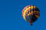 Hot Air balloon lifting off from field at sunrise