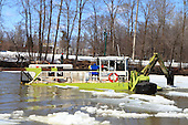 An amphibious excavator on a preventive ice breaking operation on the L'Assomption river in Joliette, Quebec