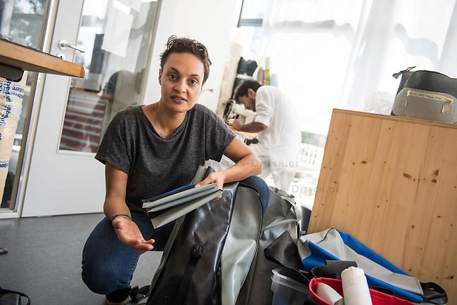 Das Berliner Start-up &quot;mimycri&quot; produziert Taschen aus den Gummiplanen gestrandeter Fluechtlingsboote.<br /> Statt Griechenlands Straende im Muell der gestrandeten Fluechtlingsboote ersticken zu lassen, stellt das Berliner Unternehmen &quot;mimycri&quot; daraus Taschen und Rucksaecke her und bietet Fluechtlingen eine Chance auf Normalitaet und Regelmaessigkeit.<br /> Im Bild: Nora Azzaoui, 30-Jaehrige Unternehmensberaterin aus Berlin, mit einem Rucksack aus dem Schlauschbootmaterial. Im Hintergrund, Abid Ali, gefluechteter Schneider aus Pakistan.<br /> 8.8.2017, Berlin<br /> Copyright: Christian-Ditsch.de<br /> [Inhaltsveraendernde Manipulation des Fotos nur nach ausdruecklicher Genehmigung des Fotografen. Vereinbarungen ueber Abtretung von Persoenlichkeitsrechten/Model Release der abgebildeten Person/Personen liegen nicht vor. NO MODEL RELEASE! Nur fuer Redaktionelle Zwecke. Don't publish without copyright Christian-Ditsch.de, Veroeffentlichung nur mit Fotografennennung, sowie gegen Honorar, MwSt. und Beleg. Konto: I N G - D i B a, IBAN DE58500105175400192269, BIC INGDDEFFXXX, Kontakt: post@christian-ditsch.de<br /> Bei der Bearbeitung der Dateiinformationen darf die Urheberkennzeichnung in den EXIF- und  IPTC-Daten nicht entfernt werden, diese sind in digitalen Medien nach &sect;95c UrhG rechtlich geschuetzt. Der Urhebervermerk wird gemaess &sect;13 UrhG verlangt.]