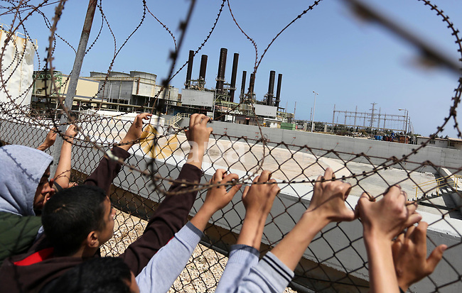 Palestinian school boys stand by a fence during a protest calling for an end to the power crisis, outside the power plant in the central Gaza Strip April 23, 2017. Photo by Ashraf Amra