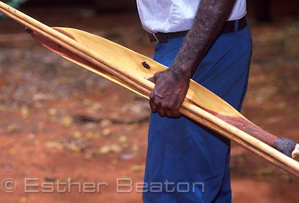An aboriginal man of Mutitjulu Community showing how to carry basic tool kit: spear with spear thrower made of mulga wood. Uluru, Northern Territory. Anangu Tours.