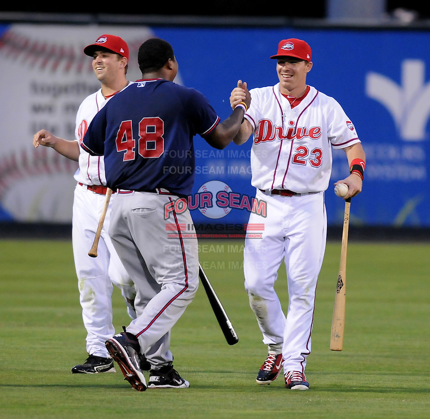 Members of the Rome Braves, including William Beckwith (48), left, and Greenville Drive, including Matt Marquis (23), celebrate the end of a mock battle, attacking from opposite sides of the field, during a lengthy rain delay before a game on July 5, 2012, at Fluor Field at the West End in Greenville, South Carolina. (Tom Priddy/Four Seam Images)