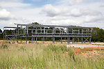 Steel frame of new building at construction site with machinery, Melton, Suffolk, England, UK