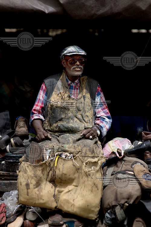 A cobbler making shoes in a city market.