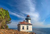 WASJ_D144 - USA, Washington, San Juan Island, Lime Kiln Point State Park, Lime Kiln Point Lighthouse and rocky shoreline beneath a cirrus filled sky.
