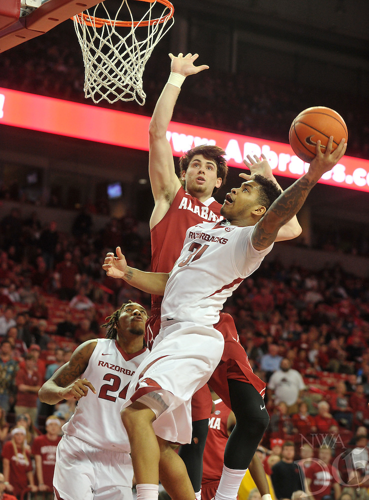 NWA Democrat-Gazette/Michael Woods --01/06/2015--w@NWAMICHAELW... University of Arkansas guard Anton Beard drives to the hoop past Alabama defender Riley Noris during the overtime period of the Razorbacks 93-91 overtime victory over Alabama during Thursday nights game at Bud Walton Arena in Fayetteville.