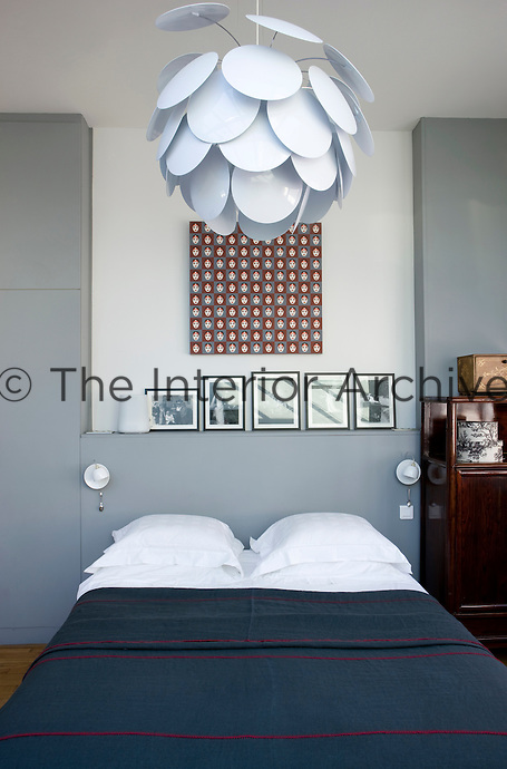 """In the master bedroom a large Christopher Mathieu """"Discoco"""" pendant light is suspended above the bed and the white ceramic bedside lamps are an Ingo Maurer design"""