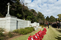 A military laying a wreath of poppies at the Cross of Sacrifice during the Remembrance Sunday ceremony at the Hodogaya, Commonwealth War Graves Cemetery in Hodogaya, Yokohama, Kanagawa, Japan. Sunday November 12th 2017. The Hodagaya Cemetery holds the remains of more than 1500 servicemen and women, from the Commonwealth but also from Holland and the United States, who died as prisoners of war or during the Allied occupation of Japan. Each year officials from the British and Commonwealth embassies, the British Legion and the British Chamber of Commerce honour the dead at a ceremony in this beautiful cemetery.