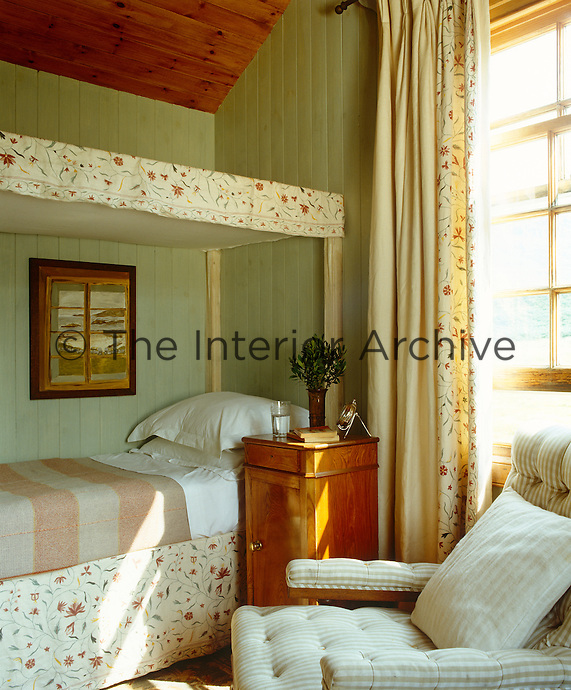 In this bedroom the bed is an unusual single four-poster in a fabric by Robert Kime