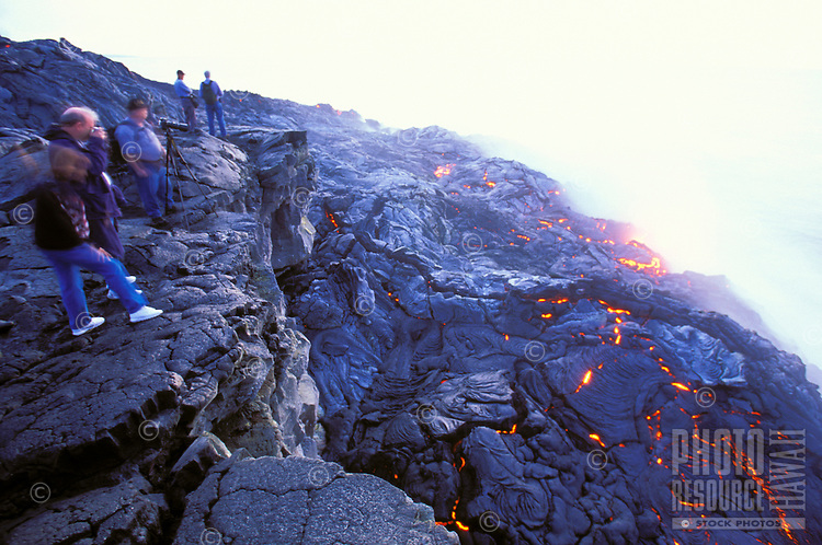 Spectators watching lava flow from Kilauea, the worlds most active volcano as it enters the sea