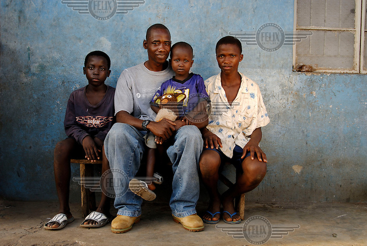 40 year old Mohammed Kamara sits with his two sons (sitting either side of him) and his three year old nephew Ibrahim Tarawallie, who Mohammed cares for since the death of his mother in childbirth. Sierra Leone has the highest maternal mortality rate in the world, with one in every eight women dying in childbirth....