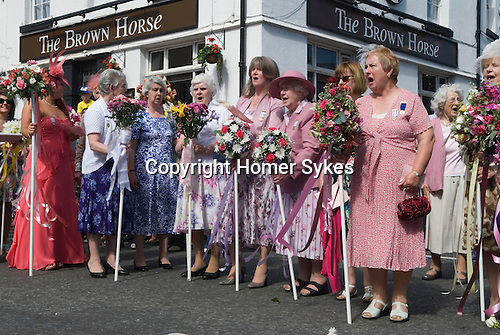 """Neston Female Friendly Society Annual Club Walking Day. Neston Cheshire UK 2015. Members at the """"Cross"""", sing hyms and Land of Hope and Glory."""