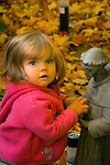Toddler hugging statue of St. Francis in autumn.