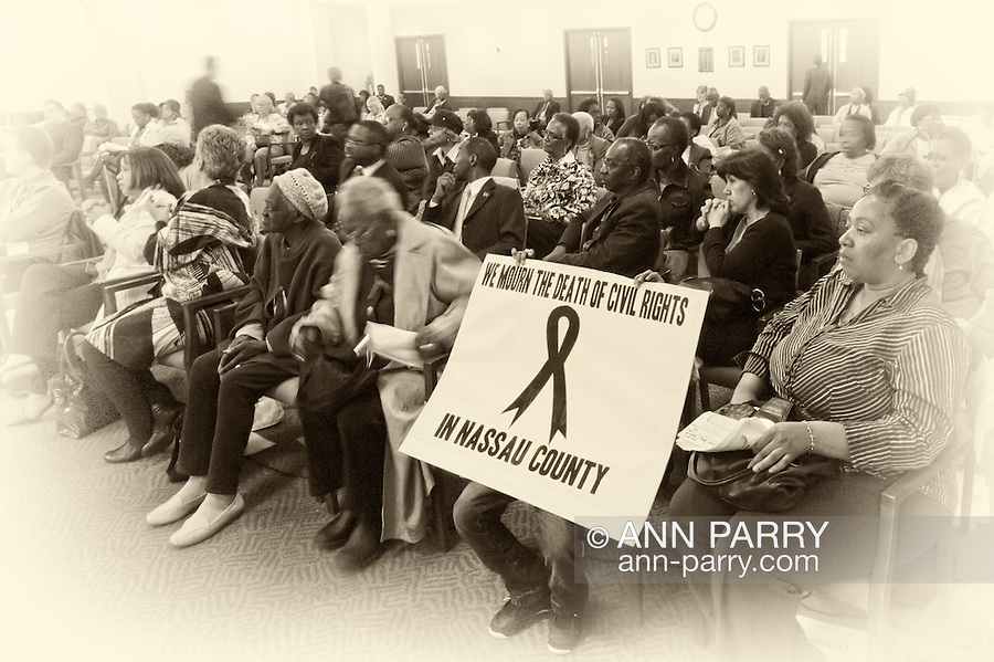 """MAY 9, 2011 - MINEOLA, NY: Young boy, Ramel Smith Jr, sitting with his face covered by sign he's holding up high, with ribbon drawn in middle and the message: """"We Mourn the Death of Civil Rights in Nassau County"""" at Nassau County Legislature's public hearing on Legislative Redistricting. S At Nassau County Executive and Legislative Building, 1550 Franklin Avenue, Mineola, New York, USA on May 9, 2011"""