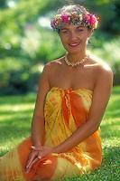 A smiling, beautiful Polynesian woman wearing haku lei and sarong sits on the grass.